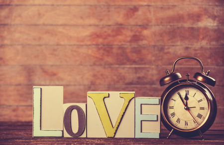 Alarm clock and word Love on wooden table. photo