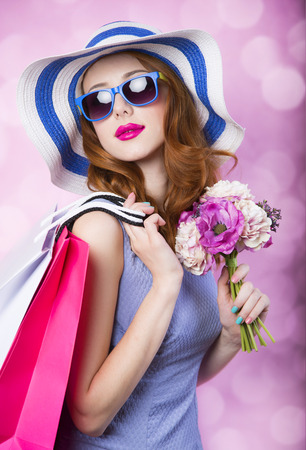 hang body: Redhead girl with shopping boxes and flowers on pink background. Stock Photo