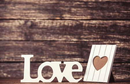 Word Love and frame for photo on wooden table. photo