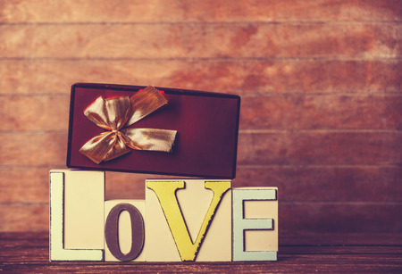 Little gift and word Love on wooden table. photo