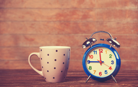 Cup of coffee and alarm clock on wooden table. photo
