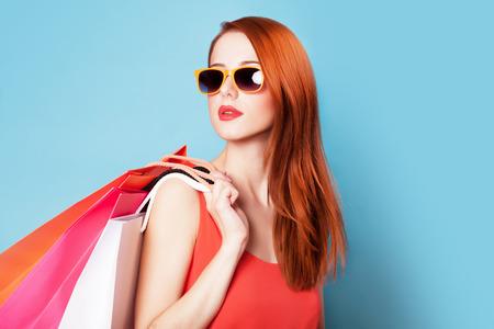 赤毛青い背景に買い物袋を保持する女性のスタイルします。