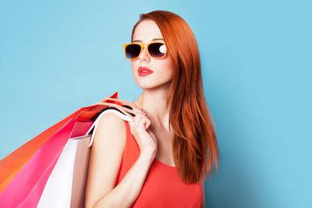 sexy young girls: Style redhead women holding shopping bags on blue background.
