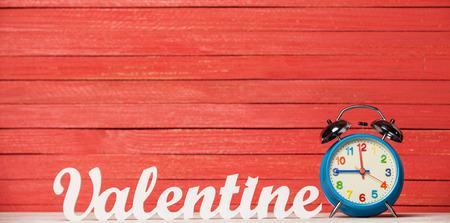 Wooden word Valentine and alarm clock. photo