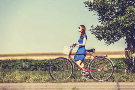 Redhead girl with bicycle on country road. photo