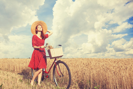 bicycle girl: Redhead peasant girl with bicycle on wheat field. Stock Photo