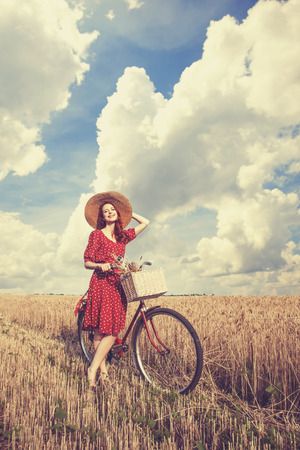 Redhead peasant girl with bicycle on wheat field. Stock Photo