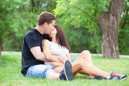 Young teen couple kissing at outdoor photo