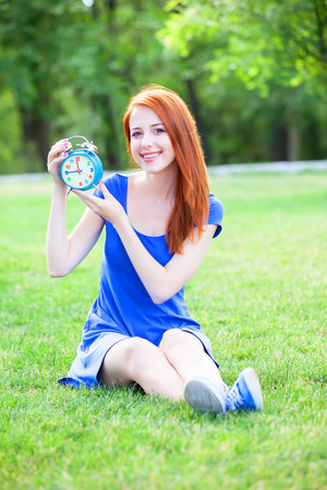 Redhead girl with clock in the park. photo