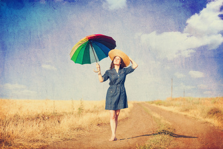 Brunette girl  with umbrella on country side road. photo