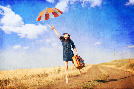 yellow umbrella: Brunette girl with suitcase on countryside. Photo in old color image style. Stock Photo