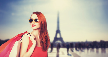 style: Redhead women with shopping bags on parisian background.