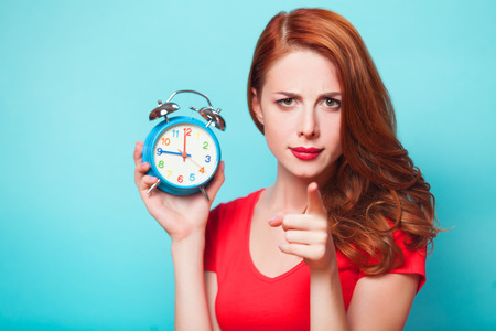 school time: Redhead girl with alarm clock on blue background  Stock Photo