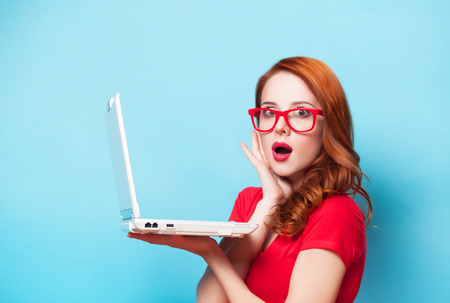 Redhead girl with laptop on blue background  Stock Photo