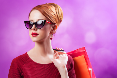 Redhead women with shopping bags on purple background. photo