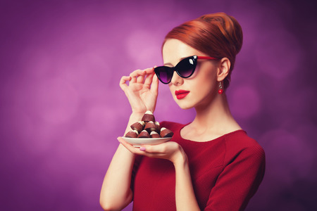 sweettooth: Redhead women with candy on violet background.