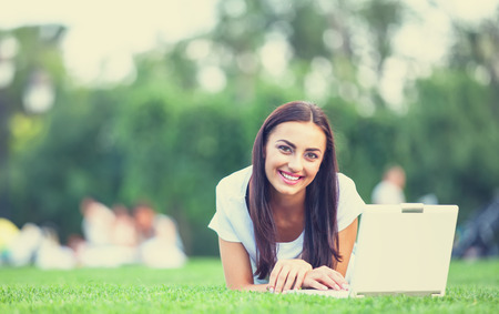1 person: Brunette girl with notebook on green grass in the park. Stock Photo