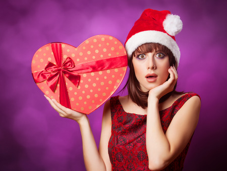 Girl in xmas hat with gift box on violet background. photo