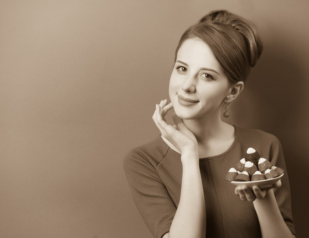 sweettooth: Women with candy. Photo in sepia color image style.