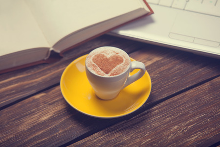 Cup of coffee with heart shape and notbook on wooden table. photo