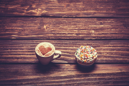 Cup of coffee and cupcake on wooden table. photo