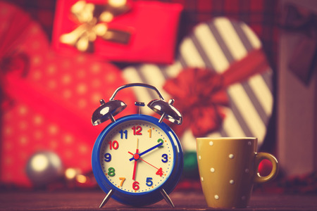 Vintage clock and cup of coffee on christmas background photo