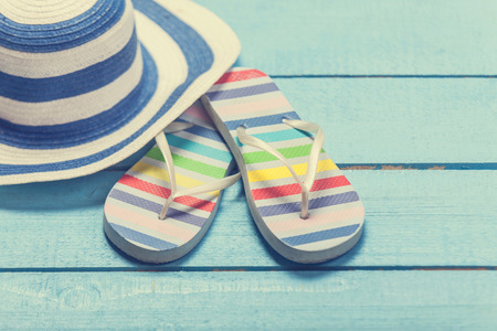swimming shoes: beach slippers and hat on blue wood