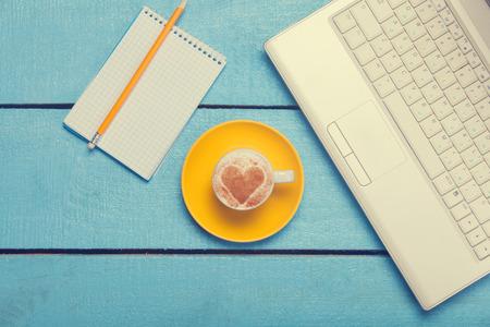 internet cafe: taza de caf� y un ordenador port�til con la nota en la mesa de madera azul.