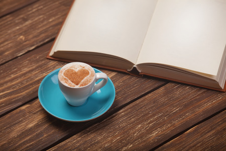 portrait orientation: Cup of coffee with heart shape and book on wooden table.