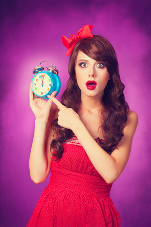 Surprised girl with alarm clock on violet background. photo