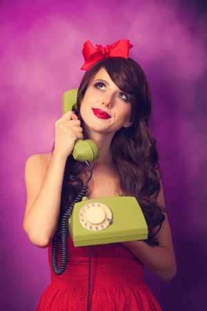 Beautiful brunette girl with telephone on violet background. Imagens