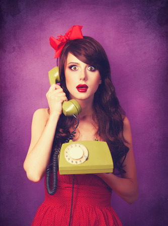 Beautiful brunette girl with telephone on violet background. photo