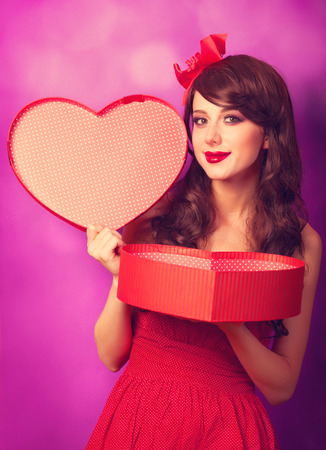Beautiful brunette girl with heart shape gift on violet background. photo