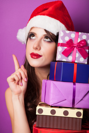 Beautiful brunette girl in christmas hat with gifts  on violet background. photo