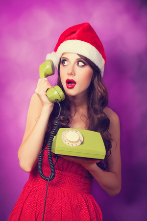 Beautiful brunette girl in christmas hat with green telephone on violet background.