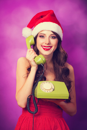 Beautiful brunette girl in christmas hat with green telephone on violet background. photo