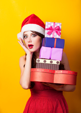 Beautiful brunette girl in christmas hat with gift on yellow background. photo