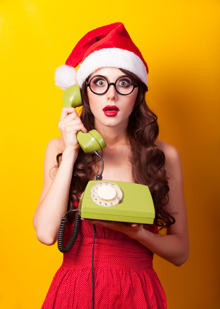Beautiful brunette girl in christmas hat with telephone on yellow background.