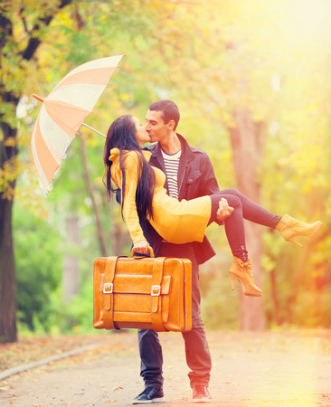 couplewith umbrella kissing outdoor in the park photo
