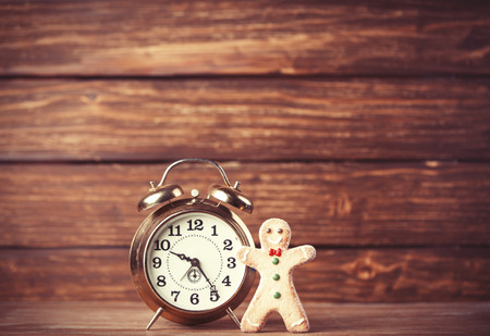 Cookie man and retro alarm clock on wooden background photo