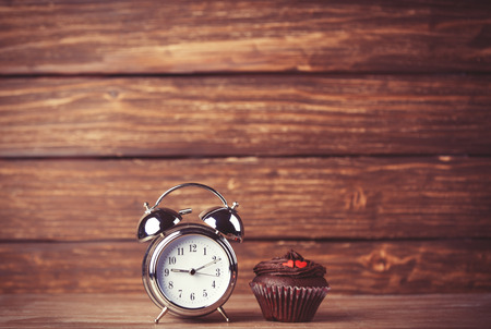 Alarm clock and cupcake. photo