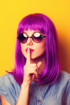 or color: Beautiful girl with violet hair in sunglasses on yellow background. Stock Photo
