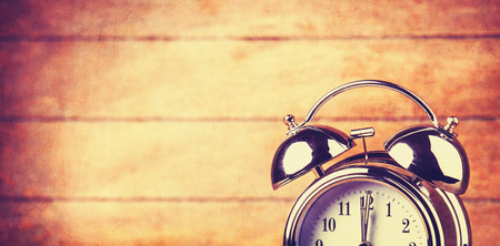 Retro alarm clock on a table. Photo in retro color image style photo