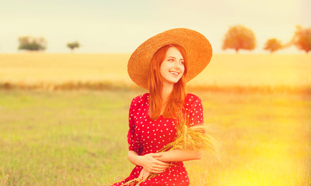 the enchantress: Redhead girl in red dress at wheat field