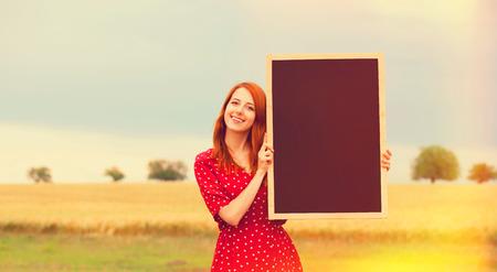 the enchantress: Redhead girl with blackboard at wheat field