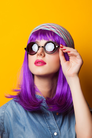 Beautiful girl with violet hair in sunglasses on yellow background. Stock Photo