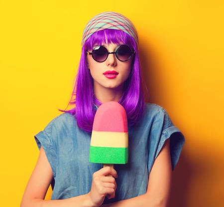 Mooi meisje met violet haar in zonnebril en ijs op gele achtergrond.