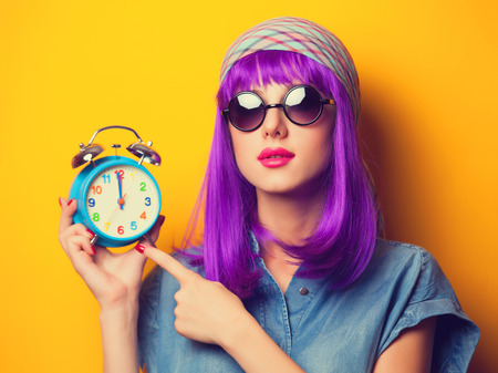 yellow shine: Beautiful girl with violet hair in sunglasses and alarm clock on yellow background. Stock Photo