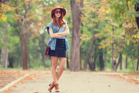 Redhead girl in sunglasses and hat in the autumn park. Stock Photo