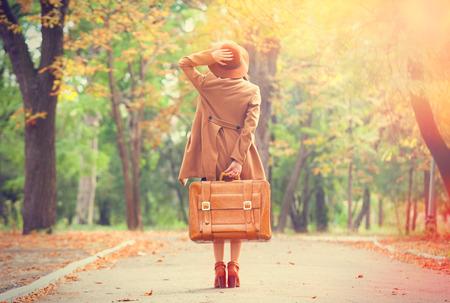 travel: 紅發女孩與手提箱在秋天的公園。 版權商用圖片